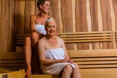 Hogere en jonge vrouw die in sauna in hitte zweten stock afbeelding