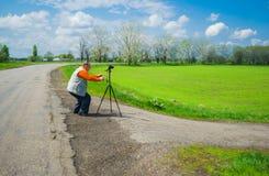 Hogere fotograaf die foto onderzoeken Stock Afbeeldingen