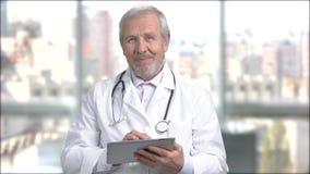 Hogere glimlachende arts met PC-tablet stock videobeelden