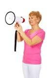 Hogere glimlachende vrouw die door een megafoon gillen Royalty-vrije Stock Afbeelding