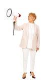 Hogere glimlachende vrouw die door een megafoon gillen Stock Foto's