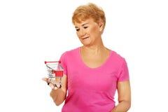 Hogere glimlachende vrouw die klein karretje houden Royalty-vrije Stock Foto