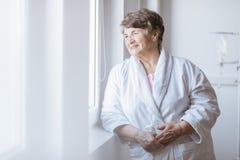 Hogere grijze dame die witte badjas dragen die zich door het venster bij verpleeghuis bevinden stock foto