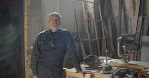 Hogere grijze haired mannelijke timmerman die bij houten vervaardiging met gekruiste wapenshorloges zich ernstig bevinden in came stock videobeelden