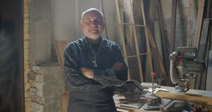 Hogere grijze haired mannelijke timmerman die zich bij houten vervaardiging met gekruiste wapens bevinden die positief in camera  stock videobeelden