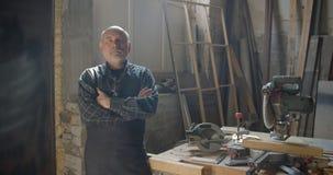 Hogere grijze haired mannelijke timmerman met baard die zich bij houten vervaardiging met gekruiste wapens bevinden die positief  stock video