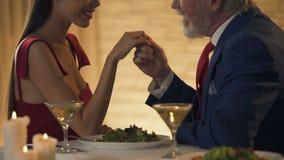 Hogere heer die zorgvuldig gelukkige hand van tedere jonge vrouw samen kussen, stock videobeelden
