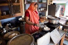 Hogere Indische dame in de kleding van Sari het koken stock foto