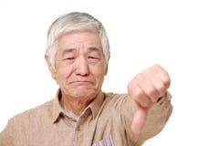Hogere Japanse mens met duimen onderaan gebaar Stock Foto's