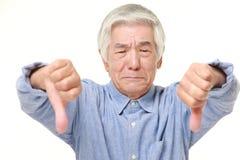 Hogere Japanse mens met duimen onderaan gebaar Royalty-vrije Stock Foto's