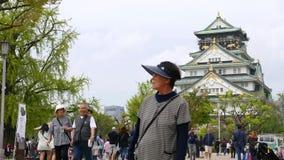 Hogere Japanse toeristen die bij Osaca-kasteel, Japan bezienswaardigheden bezoeken stock video