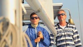 Hogere kapitein die orde geven aan bemanningslid op zeilboot, zeilen stock footage