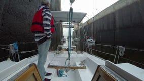 Hogere kapitein op dek, zeilboot klaar om door slot over te gaan stock video