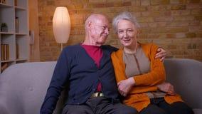 Hogere Kaukasische echtgenoten die samen bij bank zitten die thuis elkaar knuffelen die gelukkig en teder zijn stock videobeelden