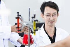 Hogere knappe en glimlachende onderzoeker die met wetenschapper spreken stock foto's
