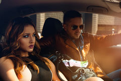 Hogere kringen sexy paar die in auto weg kijken Stock Foto's