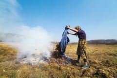 Hogere landelijke vrouw die gevallen bladeren branden Stock Afbeeldingen