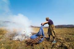 Hogere landelijke vrouw die gevallen bladeren branden Royalty-vrije Stock Foto's