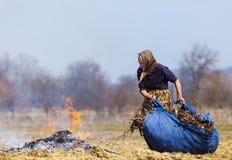 Hogere landelijke vrouw die gevallen bladeren brandt Stock Foto's