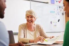 Hogere leraar bij bureau die aan volwassenenvormingsstudenten spreken royalty-vrije stock fotografie