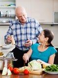 Hogere man en rijpe vrouwen kokende lunch Stock Afbeelding