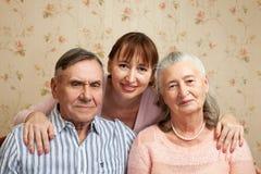 Hogere man, vrouw met hun verzorger thuis stock afbeelding