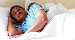 Hogere man worden die die met vrouw het snurken op bed 4k wordt gestoord stock video