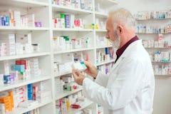 Hogere mannelijke apotheker die voor medicijnen van de plank bereiken royalty-vrije stock fotografie
