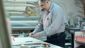 Hogere mannelijke bedrijfseigenaar die in workshop van zijn kaderstudio werken stock footage