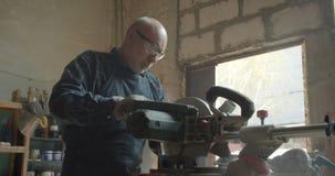 Hogere mannelijke fabrikant die bij hout met en ernstig kortzaagknipsel die werken worden geconcentreerd stock videobeelden
