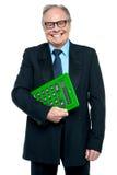 Hogere mannelijke manager die grote groene calculator houden royalty-vrije stock afbeelding