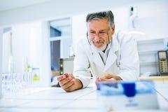 Hogere mannelijke onderzoeker die wetenschappelijk onderzoek naar een laboratorium uitvoeren Royalty-vrije Stock Fotografie