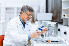 Hogere mannelijke onderzoeker die wetenschappelijk onderzoek naar een laboratorium uitvoeren Royalty-vrije Stock Foto