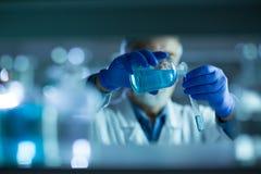 Hogere mannelijke onderzoeker die wetenschappelijk onderzoek naar een laboratorium uitvoeren stock fotografie