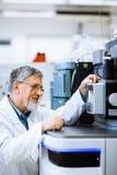 Hogere mannelijke onderzoeker die wetenschappelijk onderzoek naar een laboratorium uitvoeren Stock Foto's