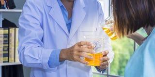 Hogere mannelijke wetenschapper en student die heldere oranje substantie mengen stock afbeelding