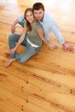 Hogere mening van paarzitting op houten vloer Royalty-vrije Stock Foto's