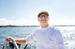 Hogere mens bij roer op boot of jacht die in overzees varen royalty-vrije stock foto's