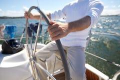 Hogere mens bij roer op boot of jacht die in overzees varen Stock Foto's