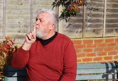 Hogere mens De vinger aan mond die, stil is wijzen op royalty-vrije stock fotografie