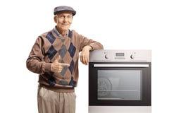 Hogere mens die aan een elektrische oven richten royalty-vrije stock foto's