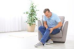 Hogere mens die aan kniepijn lijden in woonkamer stock afbeeldingen