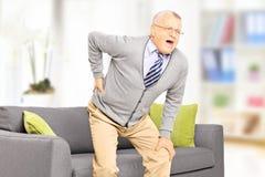 Hogere mens die aan rugpijn lijden Stock Foto's