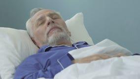 Hogere mens die in bed en slaap, gezonde correcte slaap, tijd in pensionering liggen stock video