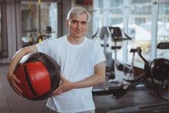 Hogere mens die bij de gymnastiek uitwerken stock foto's