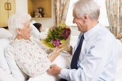 Hogere Mens die Bloemen geeft aan Zijn Vrouw in het Ziekenhuis Royalty-vrije Stock Foto