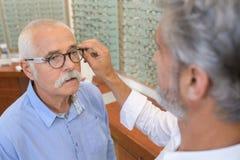 Hogere mens die bril kaders proberen bij opticien stock fotografie