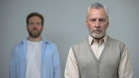 Hogere mens die camera, mannetje dat op middelbare leeftijd bekijkt, pensioenhervorming zich erachter bevindt stock video