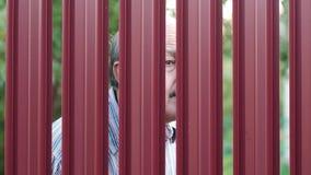 Hogere mens die door omheining kijken die op zijn buur spioneren stock videobeelden