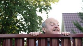 Hogere mens die door omheining kijken die op zijn buur spioneren stock footage